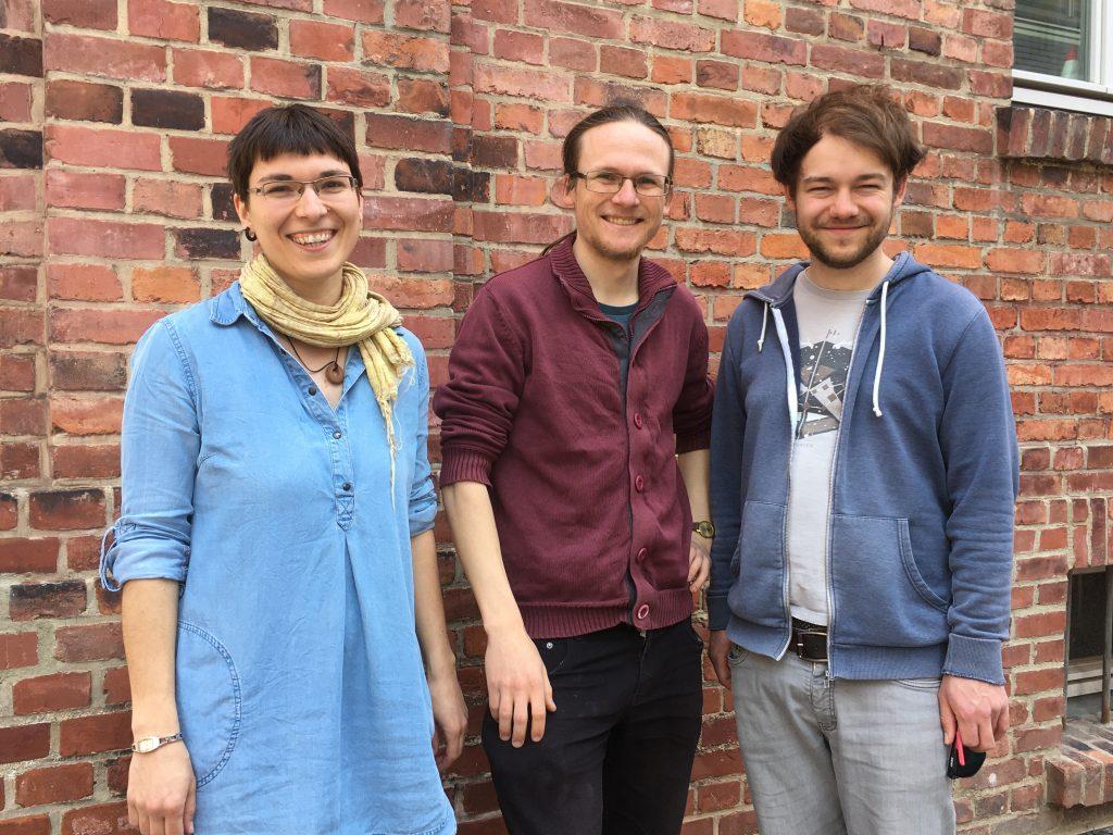 Kerstin Lopau, Arvid Jasper und Benedikt Breuer vor einer Backsteinmauer
